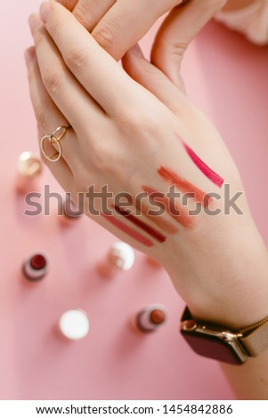 Swatch lipstick on the thin hand of a girl. Swatches of different lipsticks on the background of lipsticks on a pastel pink background #1454842886