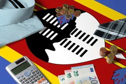 Swaziland flag on minimal money concept table. Coins and financial objects on flag surface. National economy theme.