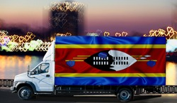 swaziland flag on the side of a white van against the backdrop of a blurred city and river. Logistics concept