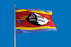 Swaziland national flag waving in the wind on a deep blue sky. High quality fabric. International relations concept.