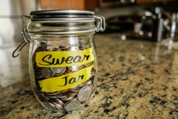 Swear Jar. A clear glass jar filed with coins and bills, saving money. The words