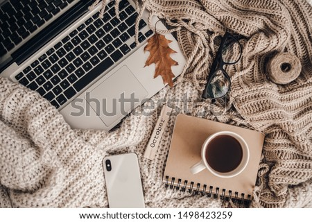 Sweaters and cup of tea with notebook, laptop and phone. Cozy autumn or winter concept.  #1498423259