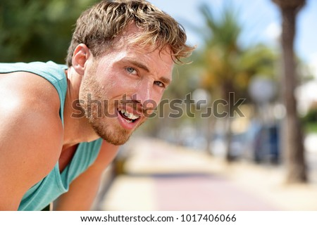 Sweating fitness man tired exausted of running in sun heat dehydrated with sweat dripping from face. Sunstroke athlete jogger jogging outside in city. Active sport lifestyle. #1017406066