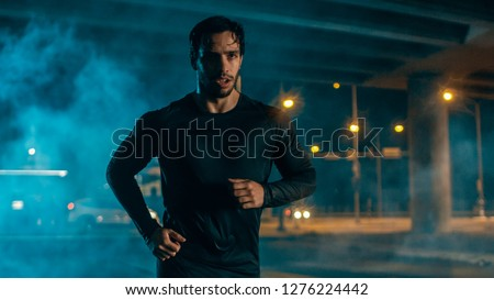 Sweating Tired Athletic Muscular Young Man in Sports Outfit Jogging in a Street Filled With Smoke. He is Running in an Evening Urban Environment Under a bridge. #1276224442
