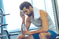 Sweaty after great work out. Handsome young men in sportswear whipping sweat with his towel and holding water bottle while sitting at gym