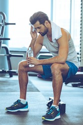 Sweaty and tired. Full length of handsome young men in sportswear whipping sweat with his towel and holding water bottle while sitting at gym