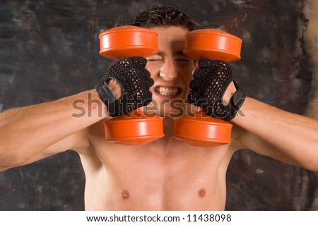 Sweaty bodybuilder training with dumbbell with droplet on his body