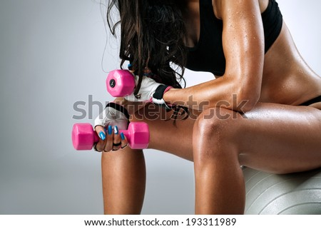 Stock Photo Sweaty female body after exercise sitting on fitness ball