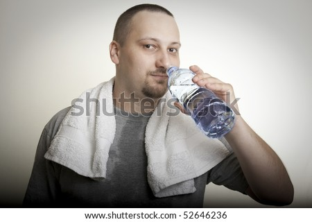 sweaty man with a white towel around his neck, drinking water after exercise