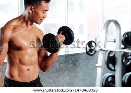 Sweaty Vietnamese sportsman lifting dumbbells when working on his biceps in gym