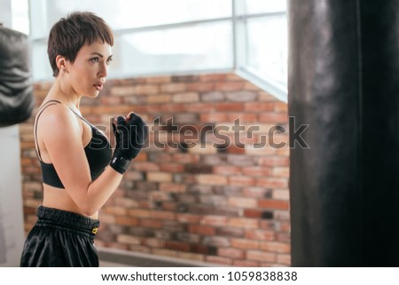 sweaty woman is working out for international boxing match indoors. self-reliance