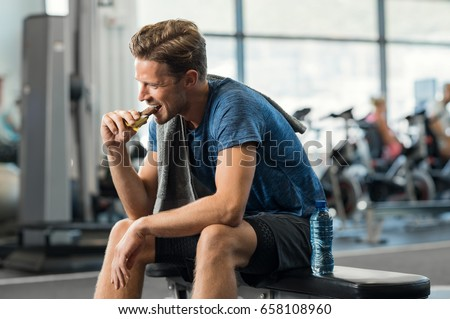 Sweaty young man eating energy bar at gym. Handsome mid guy enjoying chocolate after a heavy workout in fitness studio. Fit man biting a snack and resting on bench. #658108960