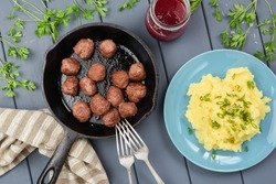 Sweden meatballs in cast iron pan, mashed potatoed with leek and berry sauce in glass jar served on gray wooden table