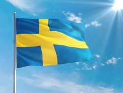 Sweden national flag waving in the wind against deep blue sky. High quality fabric. International relations concept.