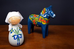 Swedish doll and wooden horse on wood surface with black background.
