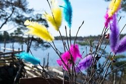 Swedish Easter birch twigs decorated with colorful feathers in yellow, blue, purple and pink and a few Easter chicken decorations. In the background is the Swedish archipelago and Baltic sea.