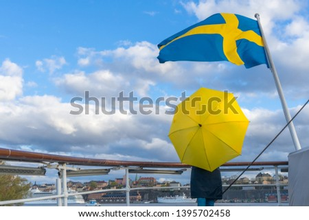 Swedish flag against blue sky with white clouds. Girl with yellow umbrella on  ship stern under beautiful swedish flag seen in Stockholm. Swedish flag fluttering in wind on the ship.