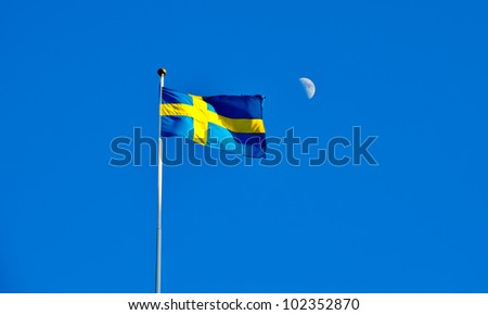 swedish flag flying against the blue sky with the moon in the background