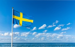 Swedish flag in the wind against a blue sky