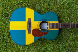 Swedish flag motif painted on wooden steel string acoustic guitar