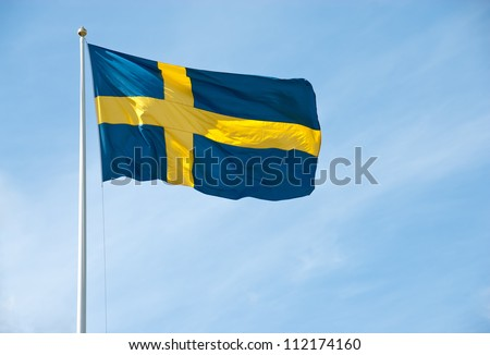 Swedish flag waving in the blue sky on a sunny day.