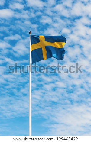 Swedish flag waving in wind against a blue sky with light white clouds, vertical