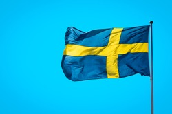 Swedish flag waving on wind on blue sky background. 6 June. Swedish Flag Day. Flag of Sweden fluttering in sunny rays high on the flagpole. Free space for text. Celebration, Holiday,  National Day.