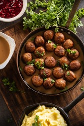 Swedish food Kottbullar meatballs, served in a pan with mashed potatoes, parsley and cranberry sauce.