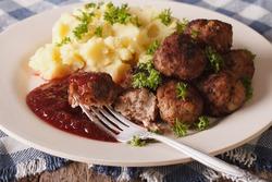 Swedish meatballs kottbullar, lingonberry sauce with a side dish mashed potato on the plate closeup. horizontal