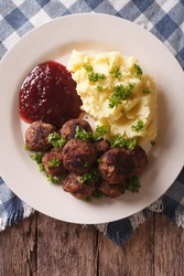 Swedish meatballs kottbullar, lingonberry sauce with a side dish mashed potato on the plate closeup. vertical view from above