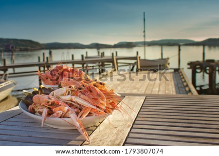 Swedish-style, simple, natural shellfish platter served on a peaceful wooden pier with the tranquil archipelago all around. Fine dining al fresco at its best on a flat calm, balmy summer's evening. Foto stock ©