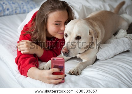 Swedish, teenage girl taking a photo with her mobile, of herself and her dog, while laying in bed