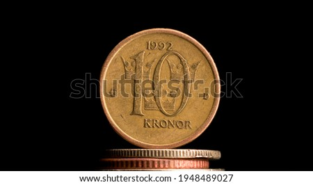 Swedish ten kronor coin, with a pitch black background. 10 SEK, svensk valuta. The Swedish king is visible on the backside, 10 written on the front. The coin is old and well used, cevered by scratches Foto d'archivio ©