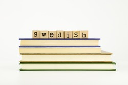 swedish word on wood stamps stack on books, language and academic concept
