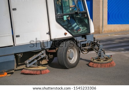 Sweeper truck industrial vehicle cleans urban road the streets of the city. Street cleaning machine at work. Conception of ecology and public services of the city. Professional scrubber brush.   #1545233306