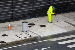 Sweeper Worker cleaning a street sidewalk with high pressure water jet machine on rainy day. Copy space