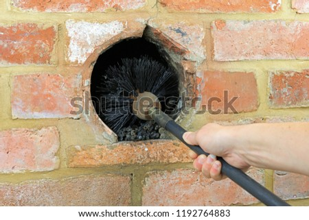 Sweeping Chimney With A Brush To Clean Out Soot Build Up.