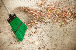 Sweeping dry leaves with broom.Autumn, fall season.Sweep the leaves, sweep people, clean the garden.Maintenance worker in park garden cleans the roads with plastic garden broom .Copy space