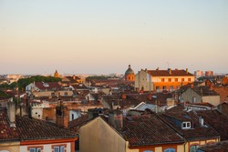 Sweeping view at dawn over the tiled roofs of old typical, Southern brick houses in the historic city centre of Toulouse, France, a densely-built area dominated by the dome of the Church of La Grave