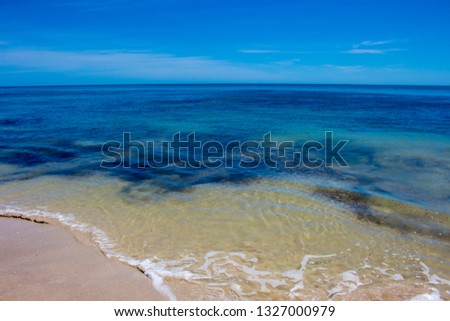 Sweeping view of the soft white sandy beach and  Indian Ocean waves gently breaking on  Hutt's Beach near Bunbury Western Australia on an  early summer afternoon is cool and inviting. #1327000979
