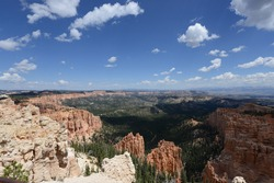 Sweeping views of the hoodoo landscape at Bryce Canyon National Park on a sunny day with puffy clouds