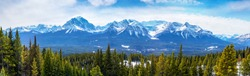 Sweeping vista of the mountain landscape showing Mount Victoria glacier of the Canadian Rockies near Banff National Park in Alberta, Canada. The Lake Louise gondola can be seen at left going up hill.