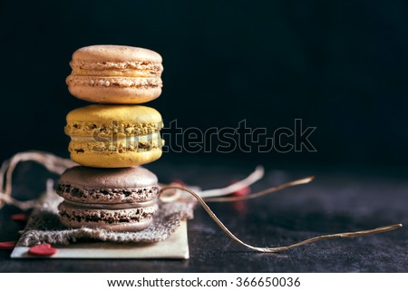 Sweet and colorful macaroon cookies tower on dark background with blank space,selective focus