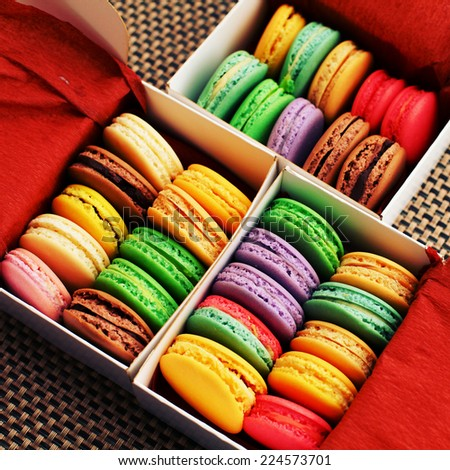 Sweet and colorful macaroons in the cardboard box with the top view. Multicolored delicious French pastries in a row with a retro vintage instagram filter.