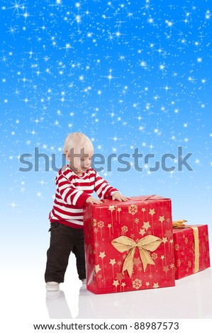 sweet and funny shot of a baby boy in red t-shirt playing with two big christmas gift box. He is standing near the big gift box and has the hands on that