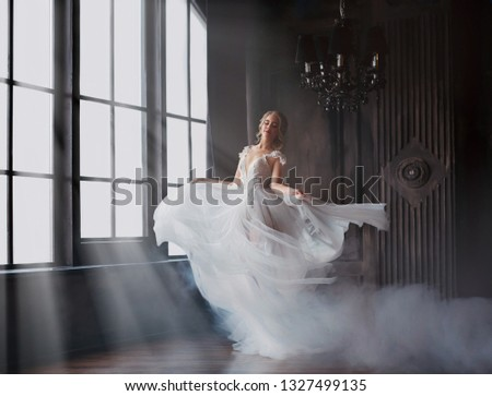 sweet and gentle girl with fair skin and blond hair dances alone in silence in an old castle, spirit of abandoned medieval building whirls in white smoke and magical thick fog in rays of sun #1327499135