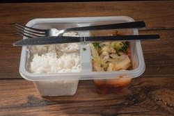 Sweet and sour chicken and white jasmine rice ready meal in a plastic container on a dark wood table surface. Metal fork and knive on top of the container.