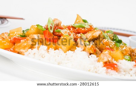 Sweet and sour chicken stir-fry on rice, with dinner settings for two
