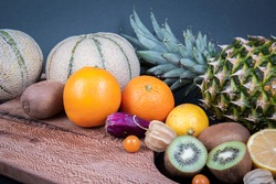 Sweet and sour fruits in a frame. A pineapple, a Barbary fig fruit, some kiwifruits, oranges, kiwifruits, honeydew melons and Chinese lantern fruits.