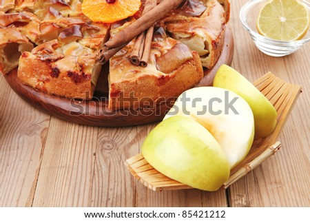 sweet apple pie cuts served with apples lemon mandarin and tea cup on wooden plate over table